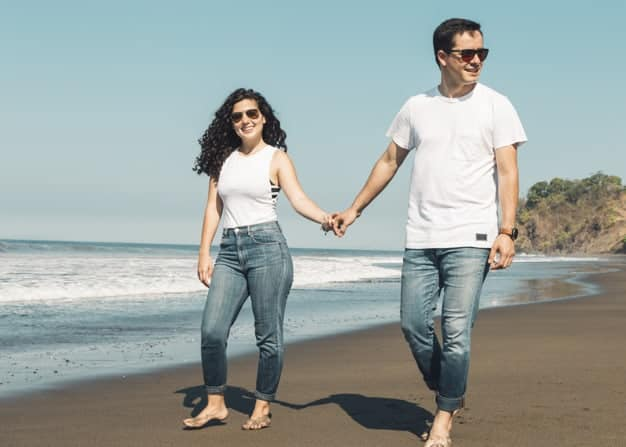 couple-walking-barefoot-sandy-beach