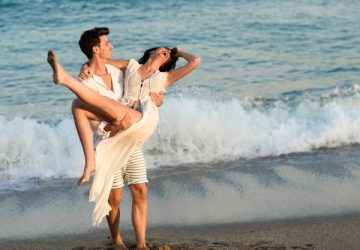 man-holding-woman-white-dress-beach